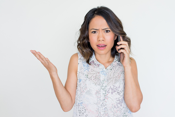 Woman on the phone appearing frustrated.
