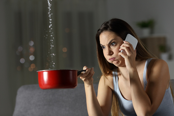Woman holding a pan under a leak in the ceiling.