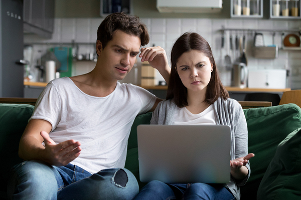 Couple sitting on a couch looking at a laptop.