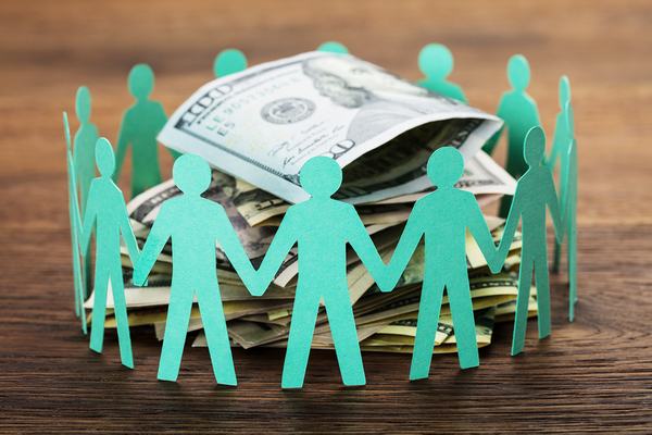 Paper cutouts of human figures in a circle around a pile of US paper money.