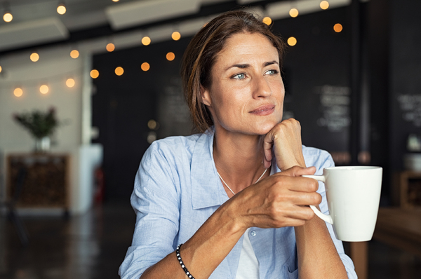 Woman sitting down with a cup of coffee.