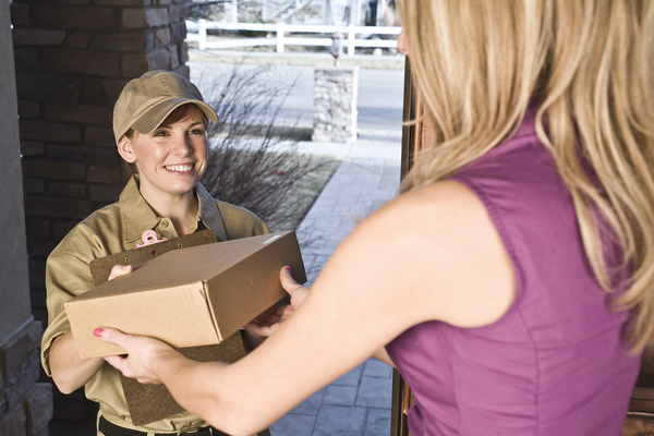 Woman receiving a package at her front door.
