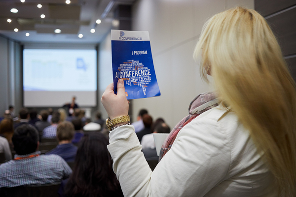 Woman at a conference holding a flyer.