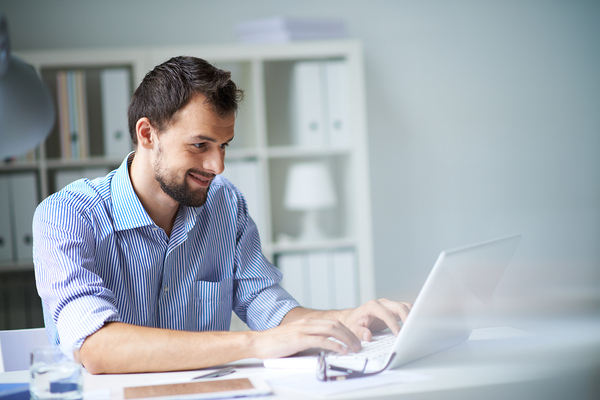 Happy bearded man using his laptop.