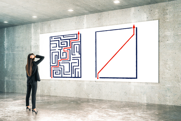 Woman looking at a wall with a painting of a maze on it.