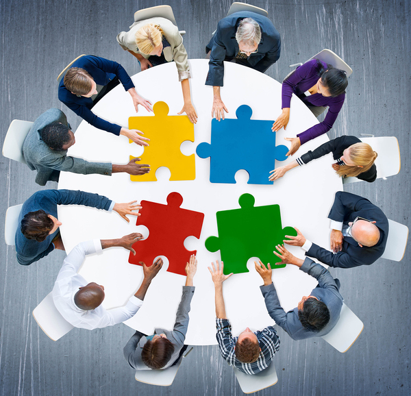 Group of people sitting around a circle table placing puzzle pieces together.