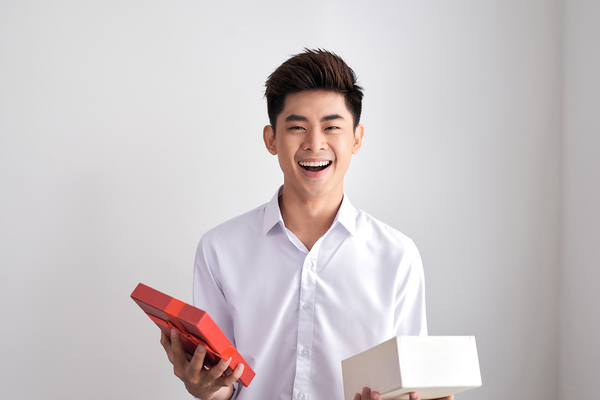 Man opening a gift box smiling.