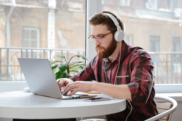 Man sitting at a table with headphones working on a laptop.