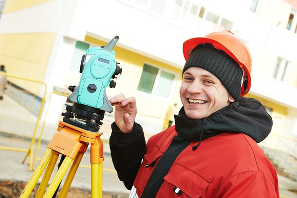 Man with a hardhat and land surveying equipment.