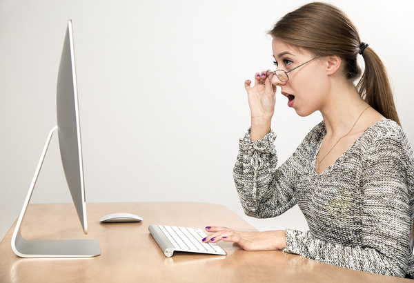 Woman working on a desktop computer looking surprised.