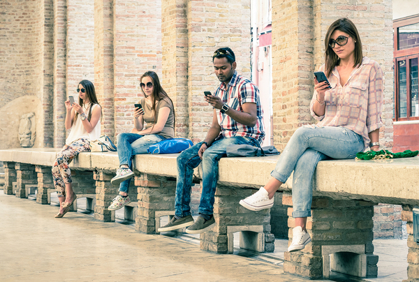 Group of people sitting on a bench looking at their phones.