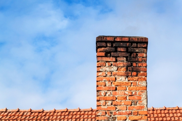 Brick chimney with black soot at the top.