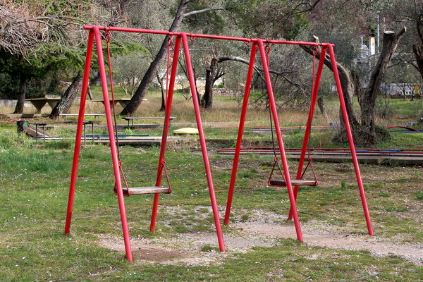 Red aluminum swing set on grass and gravel.