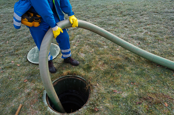 Worker pumping out a septic tank.