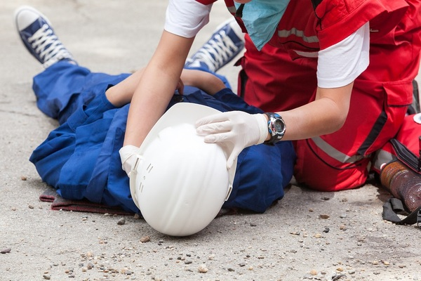Worker lying on the group with a white helmet being helped by another worker.