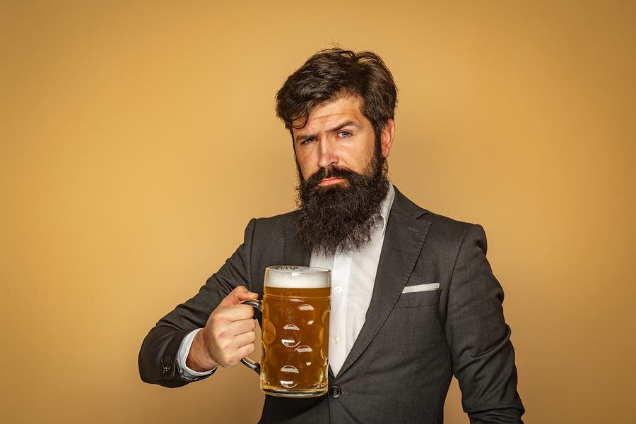 Man holding a large mug of beer.
