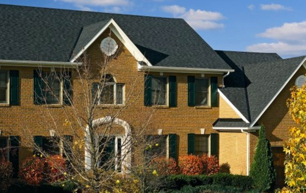 Large brick front house with dark gray shingled roof.