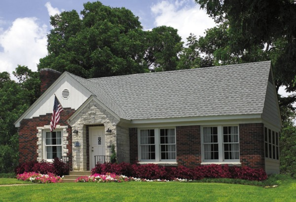 Brick front home with shingle roof and white gutters.