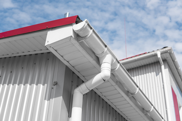 White gutters on an aluminum building with a downspout.