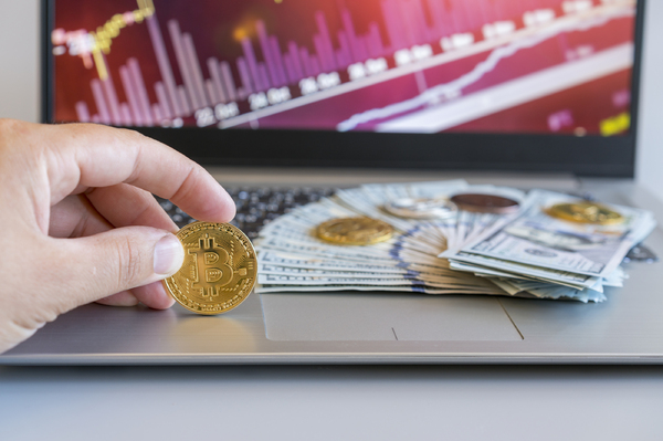 Gold coins with bitcoin symbols and paper money on a laptop computer.