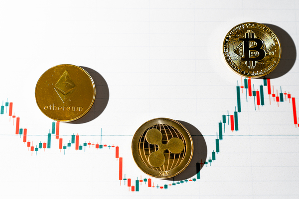 Gold coins with ethereum, ripple and bitcoin symbols.