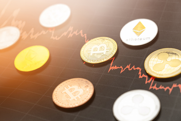 Gold and silver coins with bitcoin symbols, ripple symbols and ethereum symbols.