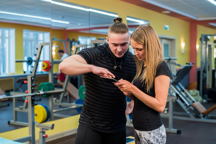 Woman and man looking at a tablet while at a gym.