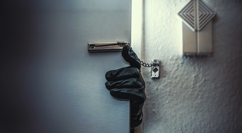 Hand with black glove opening door with chain on it.