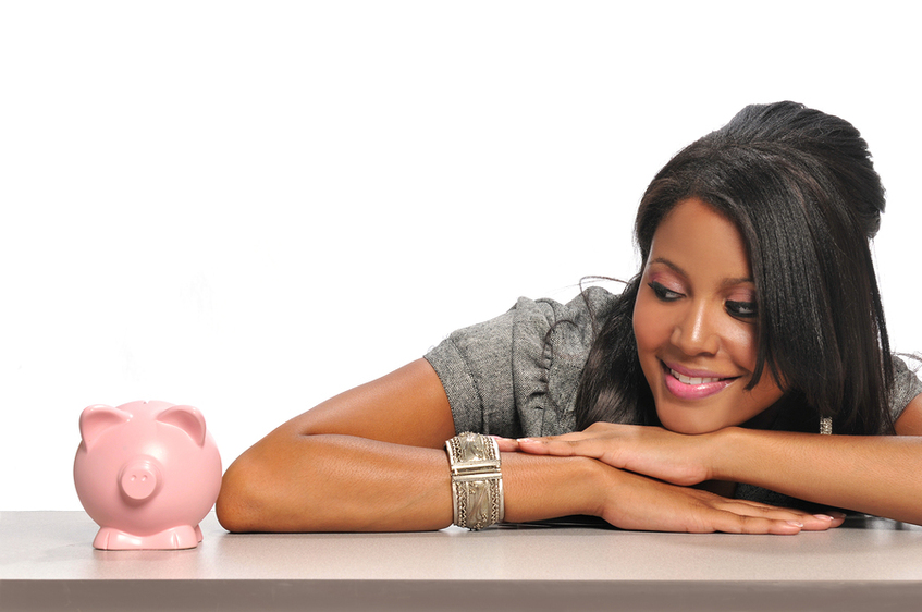 Woman looking a pink piggy bank smiling.