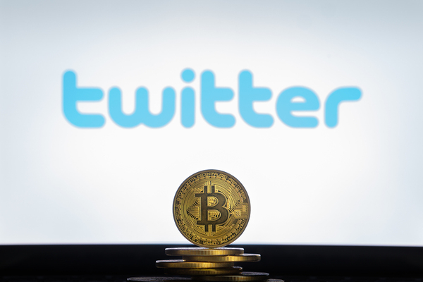 Gold coin with bitcoin symbol and twitter logo in the background.