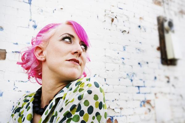 Woman with green polkadot shirt and bright pink hair.