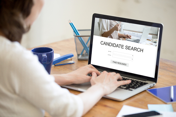 Woman typing on a laptop completing a search form for a candidate.