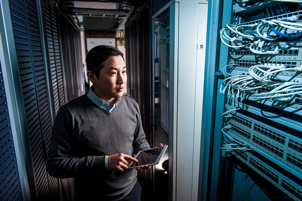 Man holding a tablet in a computer server room.