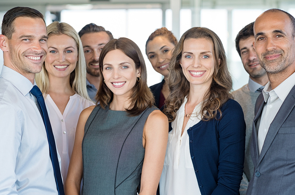 Group of people in business attire smiling.