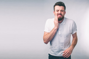 Man holding his mouth as if in pain.
