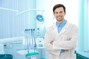 Dentist standing next to a dental chair.