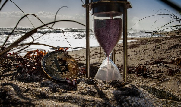 Hourglass on a beach with the gold bitcoin coin.