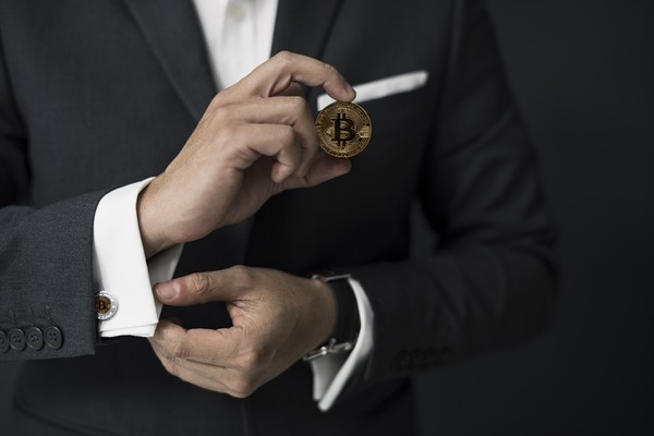 Man holding a golden bitcoin coin.