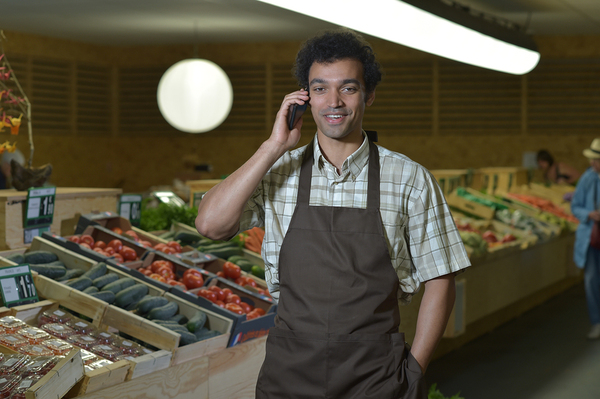 Grocery worker with a brown apron talking on a cell phone.