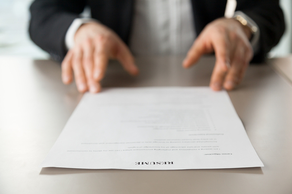 Man in a business suit looking at a resume.