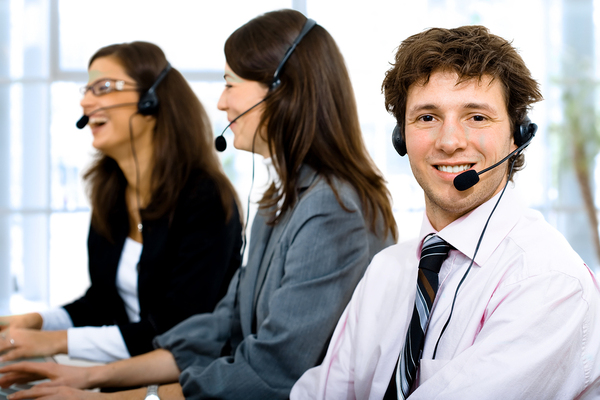 Three help desk technicians with headsets on.