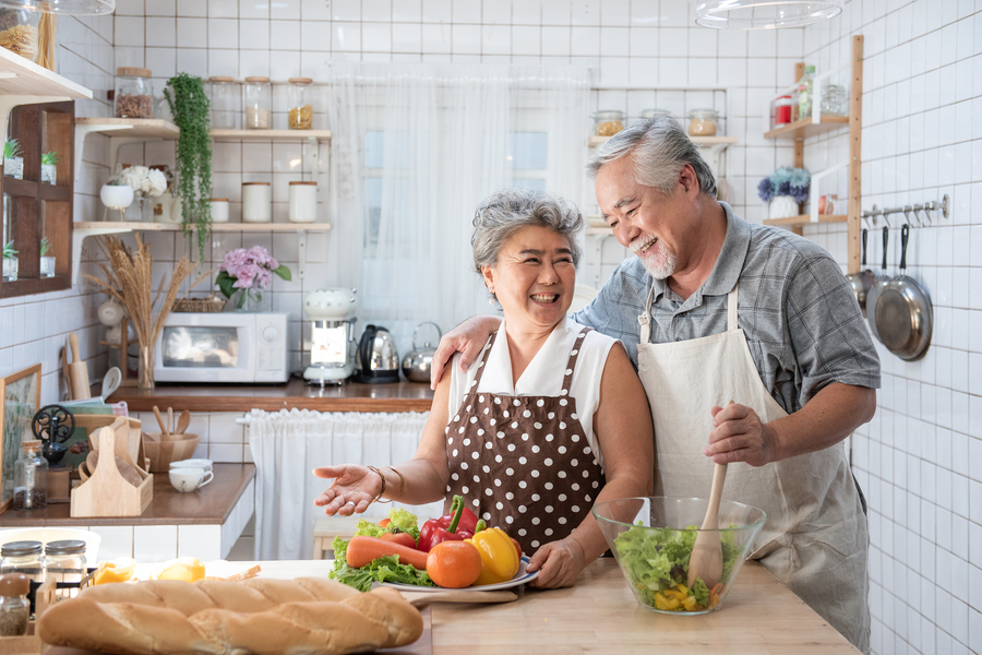 Smiling couple making a meal together.