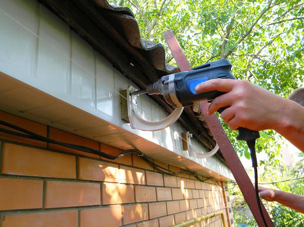Working installing a gutter system.