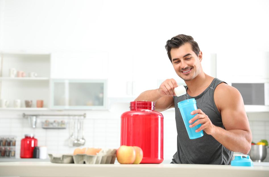 Smiling man making a protein shake.