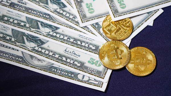 Paper money and gold coins with bitcoin symbols.
