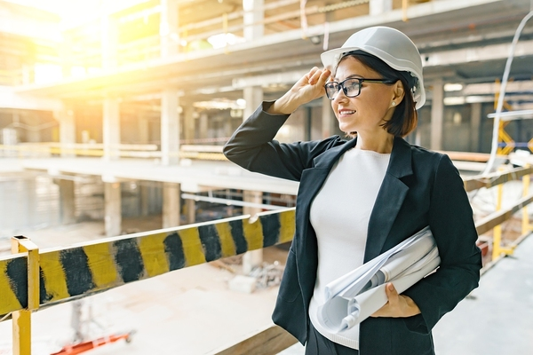 Woman wearing a hard hat at a construction site.