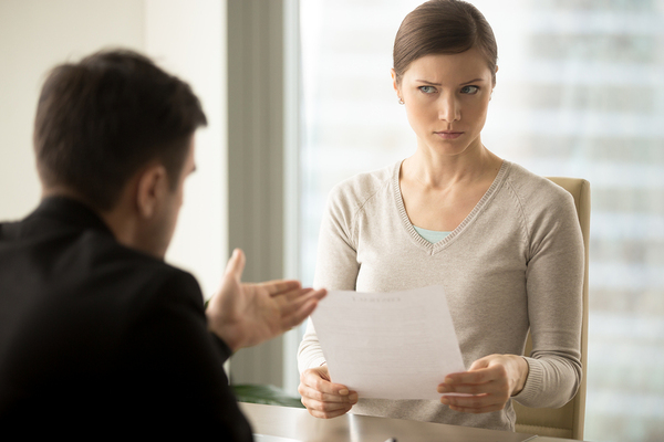 Woman looking a bit unsure as she is speaking with a colleague.