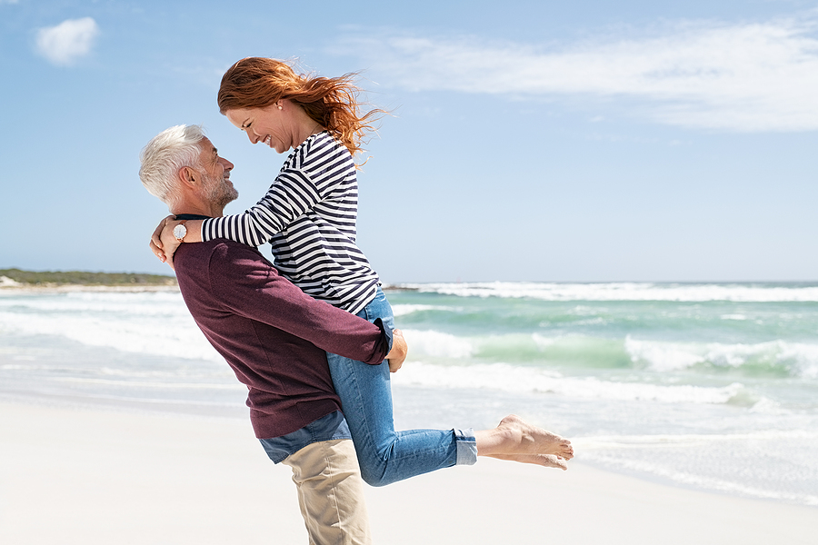 Couple at the beach hugging.