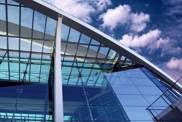 Glass building with blue sky in the background.