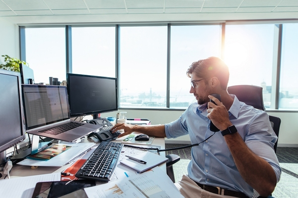 Intrapreneur working at a desk while talking on the phone.